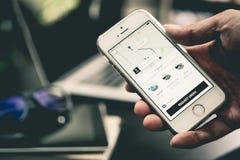 O homem de negócio está usando a aplicação de Uber em seu iPhone fotos de stock royalty free