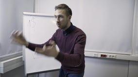 O homem de negócio executa um relatório no flipchart vídeos de arquivo