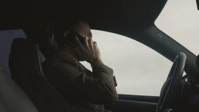 O homem de negócio fala pelo telefone que senta-se no carro video estoque