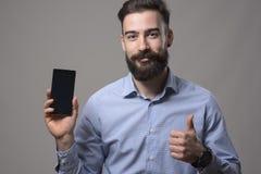 O homem de negócio farpado feliz novo que anuncia a tela esperta vazia do telefone que sorri na câmera com polegares levanta o ge Fotos de Stock Royalty Free