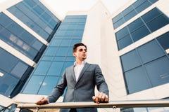 O homem de negócio fora na frente do centro de negócios toma uma ruptura da tarde fora fotos de stock royalty free