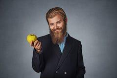 O homem de negócio guarda uma maçã verde e sorrisos imagens de stock