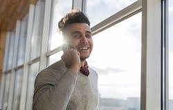 O homem de negócio latino-americano fala o suporte do telefonema no homem de negócios de Front Panoramic Window Happy Smiling Foto de Stock Royalty Free