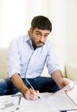 O homem de negócio mexicano espanhol preocupou contas pagando no sofá Imagem de Stock Royalty Free