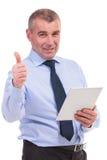 O homem de negócio mostra o polegar acima com tabuleta à disposição Imagens de Stock Royalty Free
