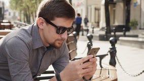 O homem de negócio nos óculos de sol usa o smartphone para trabalhar na manhã ensolarada na cidade vídeos de arquivo