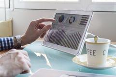 O homem de negócio novo entrega a verificação de dados na tela e no café da tabuleta na mesa de vidro Foto de Stock Royalty Free