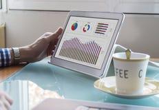 O homem de negócio novo entrega a verificação de dados na tela e no café da tabuleta na mesa de vidro Fotografia de Stock Royalty Free