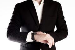 O homem de negócio olha seu relógio verificando o tempo isolado no fundo branco Foto de Stock