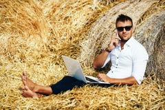 O homem de negócio olha trabalhos bonitos com um portátil e fala no telefone que senta-se no monte de feno Foto de Stock Royalty Free