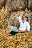 O homem de negócio olha trabalhos bonitos com um portátil e fala no telefone que senta-se no monte de feno Fotos de Stock Royalty Free