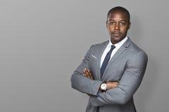 O homem de negócio preto seguro bem sucedido com braços dobrou a vista forte Foto de Stock