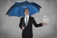 O homem de negócio protege sua casa Fotografia de Stock