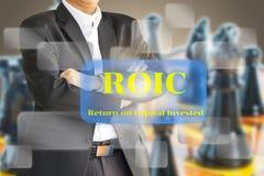 O homem de negócio que considera o ROIC, retorno no capit investido Fotografia de Stock