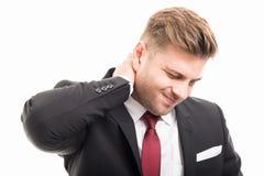 O homem de negócio que está guardando o pescoço gosta de ferir foto de stock