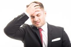 O homem de negócio que está guardando a testa gosta de ferir foto de stock