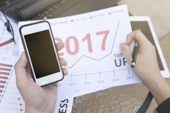 O homem de negócio que usam o portátil e o smartphone e a tabuleta pelo ano financeiro analítico 2017 do gráfico tendem a previsã Imagem de Stock
