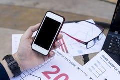 O homem de negócio que usam o portátil e o smartphone pelo ano financeiro analítico 2017 do gráfico tendem a previsão que planeia Fotografia de Stock Royalty Free