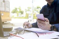 O homem de negócio que usam o portátil e o smartphone pelo ano financeiro analítico 2017 do gráfico tendem a previsão que planeia Imagens de Stock