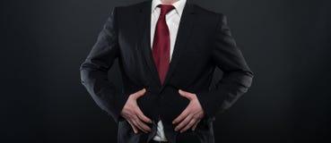 O homem de negócio que veste o terno preto que guarda a barriga gosta de ferir fotografia de stock royalty free