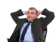 O homem de negócio senta-se na cadeira com mãos atrás da cabeça Fotografia de Stock