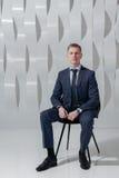 O homem de negócio senta-se na cadeira no escritório moderno Imagem de Stock