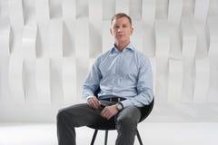 O homem de negócio senta-se na cadeira no escritório urbano moderno Foto de Stock