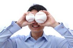 O homem de negócio toma a esfera dois na face Imagens de Stock Royalty Free