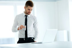 O homem de negócio trabalha em seu computador no escritório Fotografia de Stock