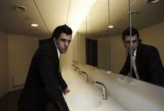 O homem de negócio vão que verific seu olha no espelho Foto de Stock Royalty Free