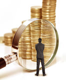 O homem de negócio verifica o dinheiro com a lupa imagens de stock royalty free