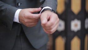 O homem de negócios à moda endireita os punhos de seu revestimento vídeos de arquivo
