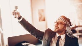 O homem de negócios árabe de sorriso aumentou a ampulheta acima imagem de stock royalty free