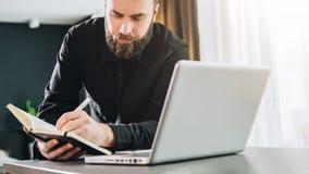 O homem de negócios é o computador próximo ereto, funcionamento no portátil, fazendo anotações no caderno Observação do homem web fotografia de stock