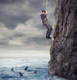 O homem de negócios é provável cair no mar com tubarões conceito dos problemas e da dificuldade no negócio imagem de stock royalty free