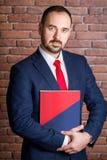 O homem de negócios abraça um dobrador a sua caixa Imagem de Stock Royalty Free