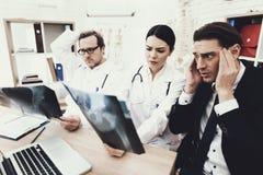 O homem de negócios adulto é horrorizado pelo diagnóstico do doutor que mantém a radiografia no escritório médico imagens de stock
