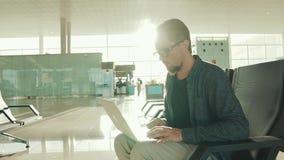 O homem de negócios adulto ocupado está datilografando no caderno no terminal do aeroporto video estoque