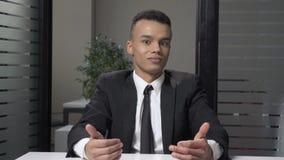 O homem de negócios africano bem sucedido novo em um terno mostra uma emoção da surpresa, agitando sua cabeça, sentando-se no esc video estoque