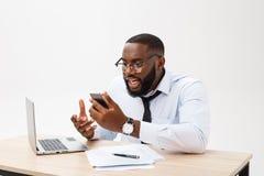 O homem de negócios africano decepcionado é ofuscado e fala confundida no telefone Sente o desacordo total sobre o negócio imagens de stock