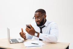 O homem de negócios africano decepcionado é ofuscado e fala confundida no telefone Sente o desacordo total sobre o negócio foto de stock