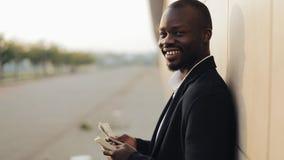 O homem de negócios afro-americano bem sucedido novo está estando na rua e está contando o dinheiro Ele que olha no vídeos de arquivo