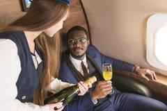 O homem de negócios afro-americano bem sucedido novo nos vidros e em uma comissária de bordo mostra uma garrafa do vinho na cabin fotografia de stock royalty free