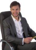 O homem de negócios no escritório senta-se em uma cadeira imagens de stock royalty free