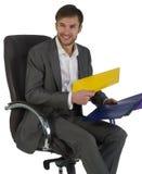 O homem de negócios no escritório senta-se em uma cadeira imagem de stock royalty free