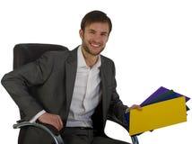 O homem de negócios no escritório senta-se em uma cadeira fotografia de stock royalty free