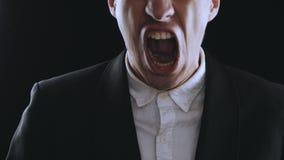 O homem de negócios agressivo em um terno é gritando e mostrando a raiva em um fundo preto Saliência irritada O perigo de video estoque