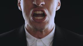O homem de negócios agressivo em um terno é gritando e mostrando a raiva em um fundo preto Saliência irritada O perigo de filme