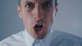 O homem de negócios agressivo na camisa branca é gritando e mostrando a raiva Conceito do chefe irritado filme