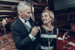 O homem de negócios ajuda a mulher a obter vestida no restaurante fotografia de stock